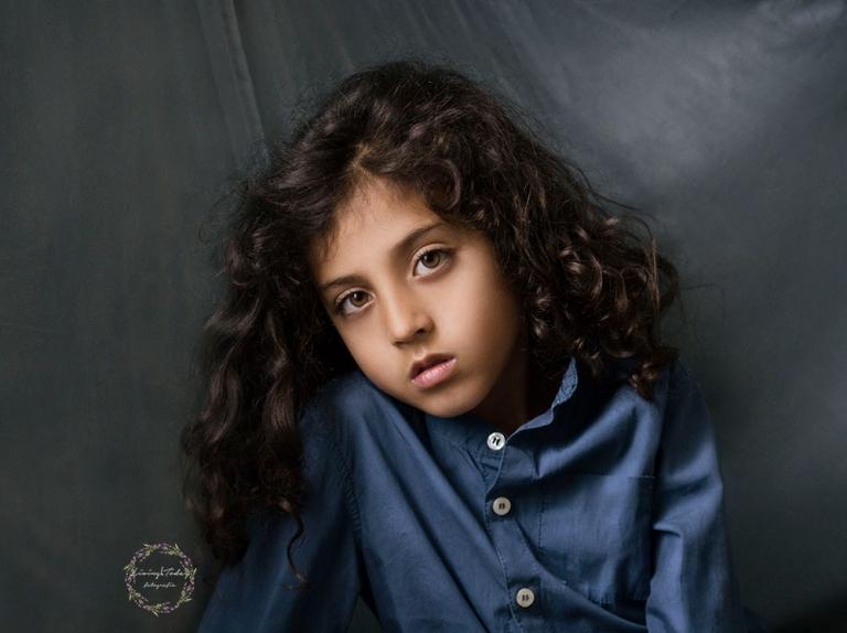 Retrato fine art de niño con cabello largo y rizado con una camisa azul