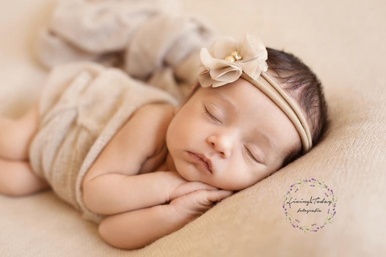 Recién nacida dormida con sus manitas juntas y una diadema color beige con perlas