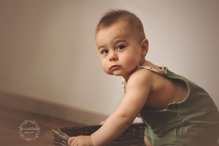 Bebé en su sesión de seguimiento vestido con peto verde.