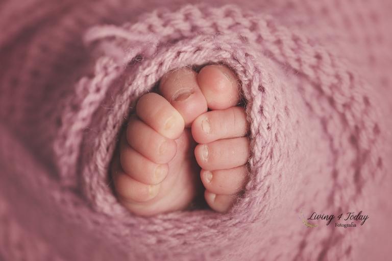 Fotografía infantil. Detalle de pies de bebé envueltos en una manta de color lila tomada en Sopelana en una sesión newborn.