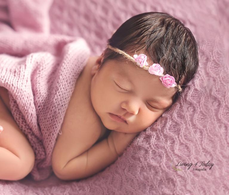 Esta es una preciosa bebe con una diadema de flores rosa sobre una manta de color lila.