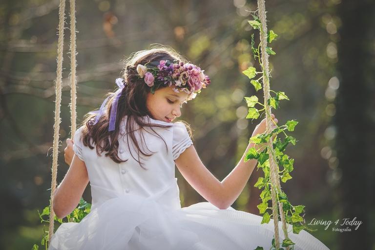 Fotografia de una niña con su vestido de comunión y una corona de flores en tonos lilas montada sobre un columpio